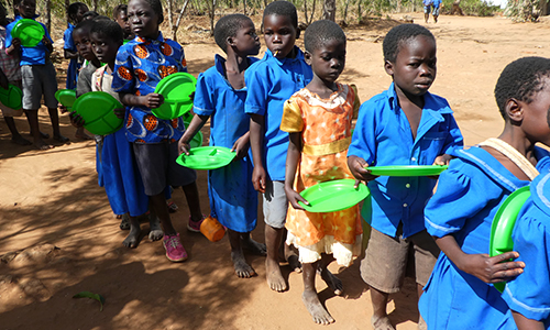 Children in Malawi lining up for meals