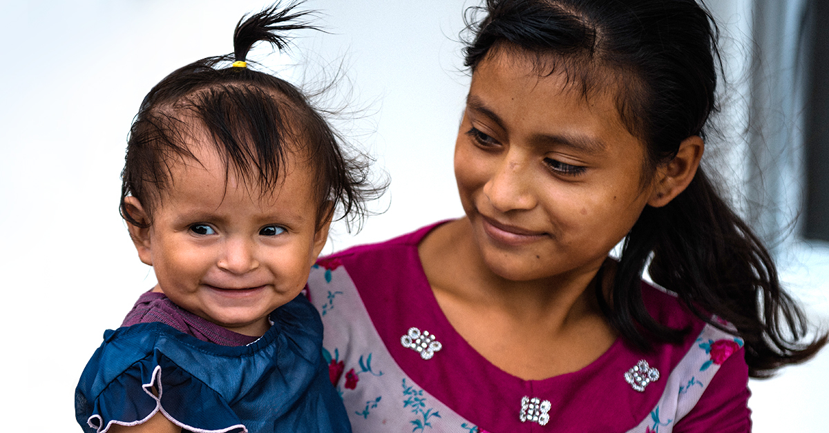 A young mother smiles at her child who has grown to be healthy.