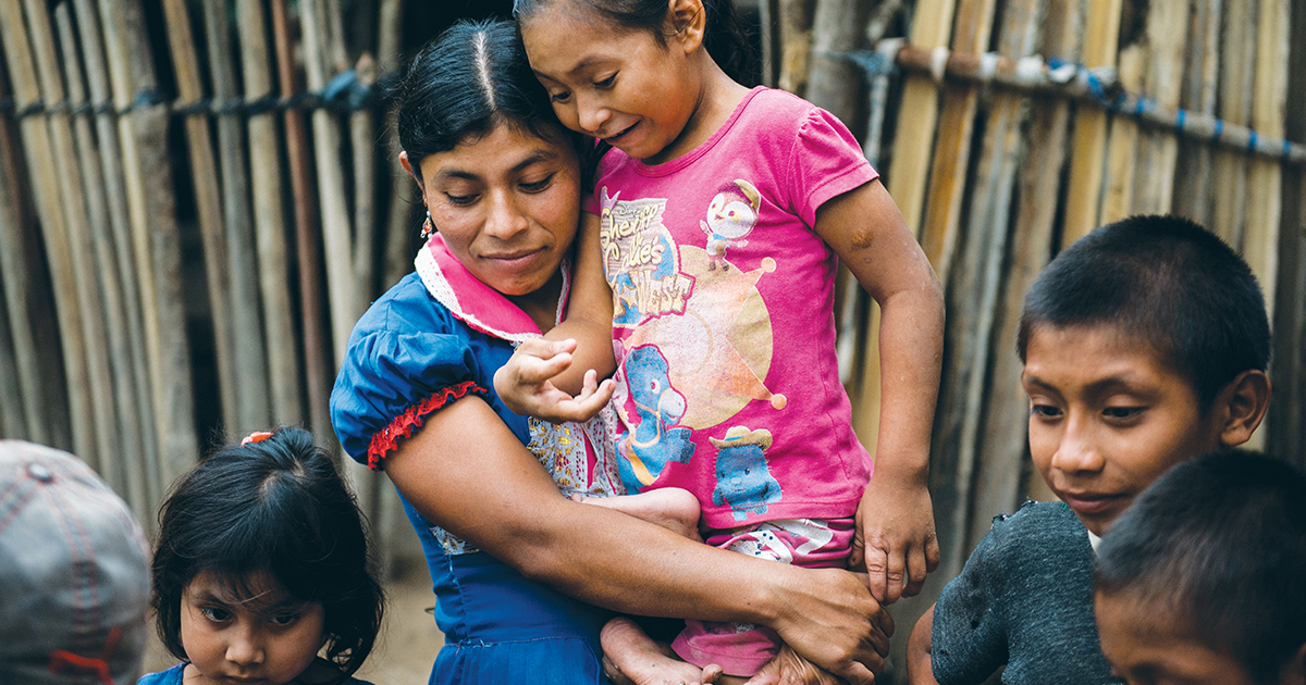 Mother holds her daughter outside of their dilapidated home.