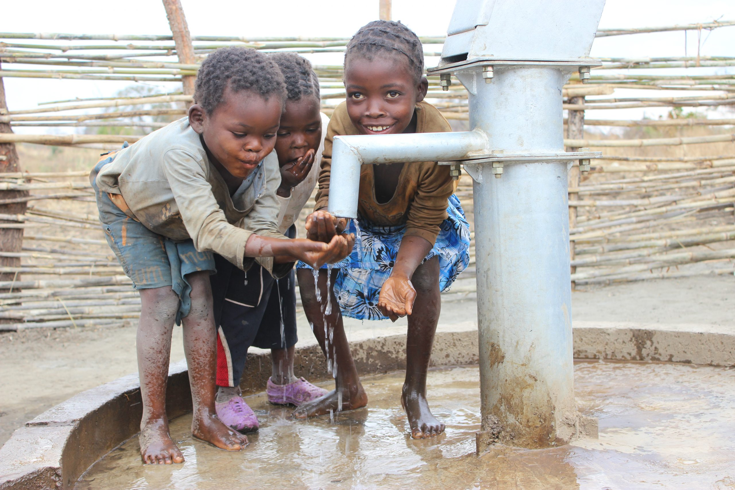 Kids drinking from water well