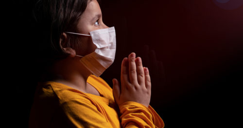 Girl wearing mask praying