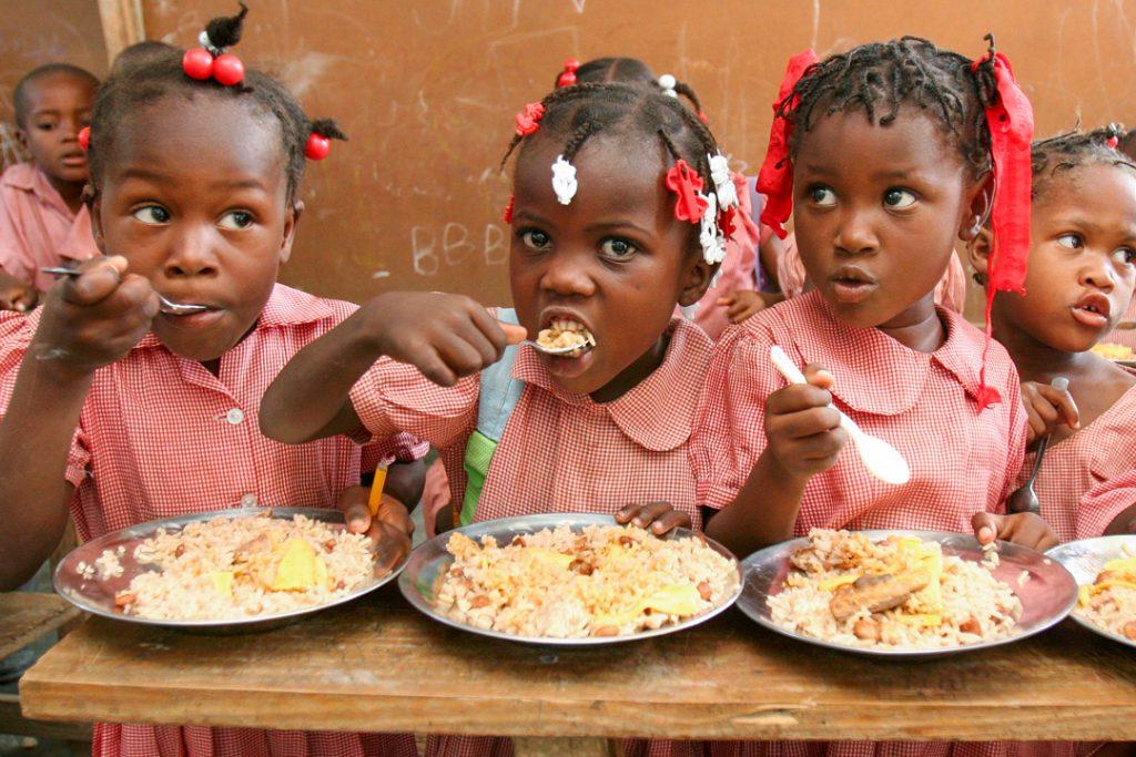 Children eating at Divine Shelter Schools feeding program