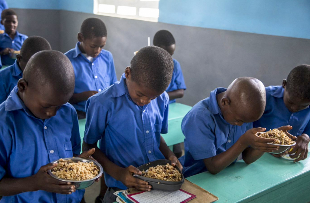 Students praying before taking lunch at school