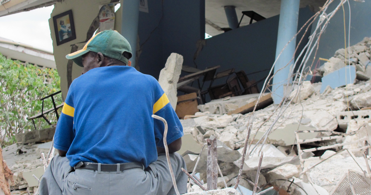 man sitting in the middle of the rubble after devastating earthquake in 2010